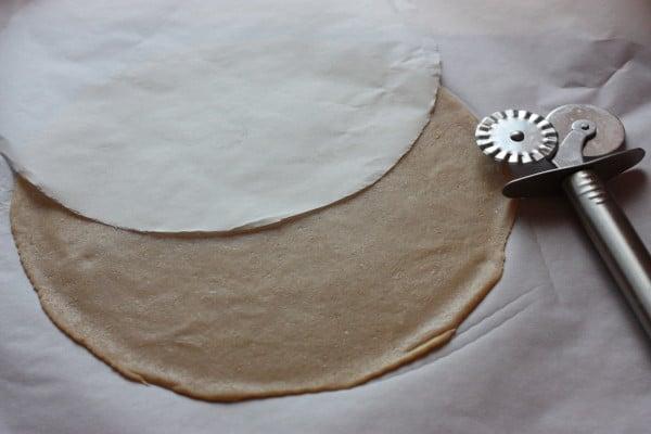 Celé cesto si odvážime (malo by mať 850/860 gramov) a rozdelíme ho na 6 rovnakých kúskov. Na pečiaci papier si obkreslíme kruh v priemere 22 cm a vystrihneme ho. Dáme si nový kus papiera na pečenie, zoberieme si jeden bochník a vyvaľkáme si ho na papieri na tenký kruh. Priložíme náš vystrihnutý kruh a koliečkom orežeme dokola a odstránime presahujúce cesto. Do orezaného kruhu spravíme koliečkom štyri zárezy (čiarky) aby nám pri pečení dýchalo.