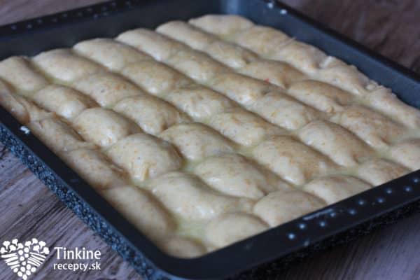 Pekáč ci poriadne vymažeme maslom. Vykysnuté cesto jemne vyberieme z misky, dáme na pekáč a rukami jemne roztlačíme rovnomerne po plechu. Zoberieme si radielko a rozrežeme cesto na 7 pásikov vodorovne a 7 zvisle, aby sme dosiahli malé buchtičky.