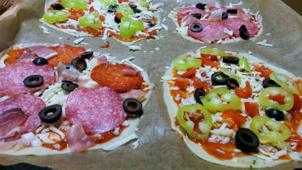 Kečup si rozotrieme na cesto, posypeme pizza korením (preferujem Vitana, bez konzervantov) a čím máte radi. Ja obľubujem zeleninovú: šampióny, paprika, olivy s hermelínom. Veľakrát prihodím nadrobno nakrájané cherry rajčinky. Vynikajúca je aj šunka, šampióny alebo salám a slaninka. Prílohu tiež, no nie veľa/kopcom. Ona má byť tenká a krehká ako snack, aby cesto nezostalo mokré.